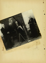 Photograph of three men standing near microphone