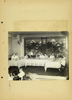 Photograph of men and women sitting at table