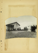 Photograph of people in a line near house