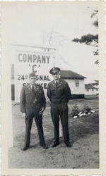 """Henri Landwirth with another soldier in front of """"Company C 24th Signal Service"""" sign"""