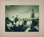 Photograph of a celebration next to rocket launch pad with President Kennedy and astronaut John Glenn sitting in the backseat of the car.