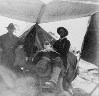 A Soldier and barber giving another soldier a shave.