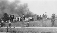 People stand along a protective brick wall looking at the Ybor City Fire of 1908.