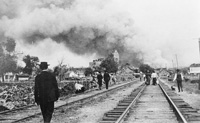 People look from the rairoad track near the Florida Brewing Company and the Ybor City Ice Works  at the Ybor Fire of 1908