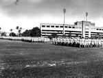 Men in uniform drilling on by the University of Florida stadium.
