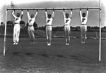 5 University of Florida cheerleaders hang from a Florida Field goalpost by their hands.