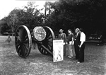 Men stand by 2 large wheels and two signs - Forestry Field Day