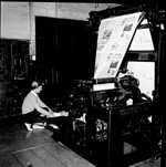 A woman lifts paper off the printing press at the University of Florida