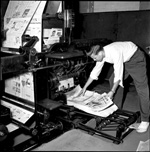 Man leans over to take The Florida Alligator copies off press