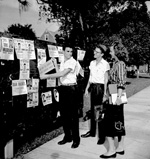 Flyers for Student Government elections being read by students on the campus of the University of Florida