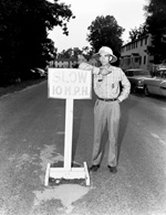 Volunteer policeman of Flavet III stands by 10 mpr sign.