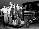 Members of the Flavet III Fire Department on the back of the fire truck on the Universtiy of Florida campus