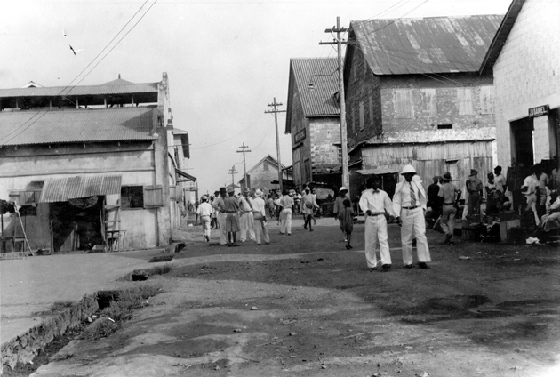 Photo: Monrovia (Water Street?). Many pedestrians, African man in white suit, pith helmet.