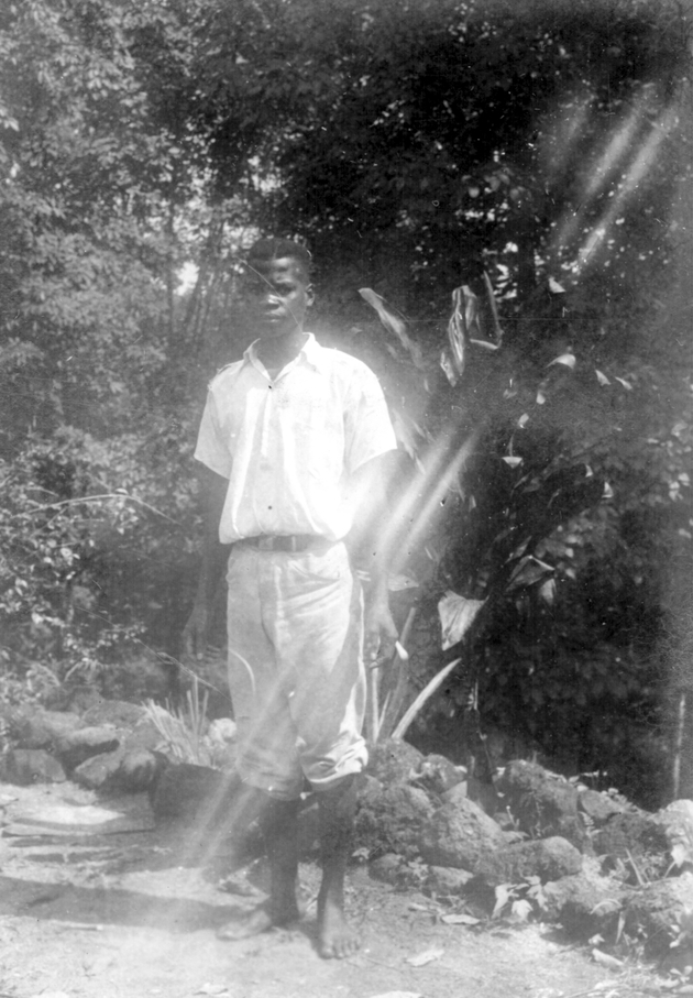 Photo: Liberian man in white shirt and pants posing.