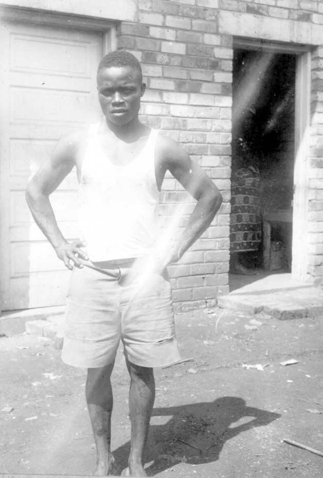 Photo: Liberian man in white shorts and t-shirt posing.