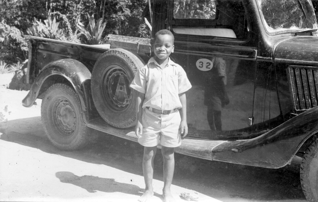 Photo: Young Liberian boy in shirt and shorts posing in front of a plantation pickup truck.