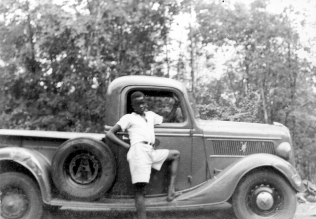 Photo: Adolescent Liberian boy in white shirt and white shorts posing with foot on running board of pickup truck.