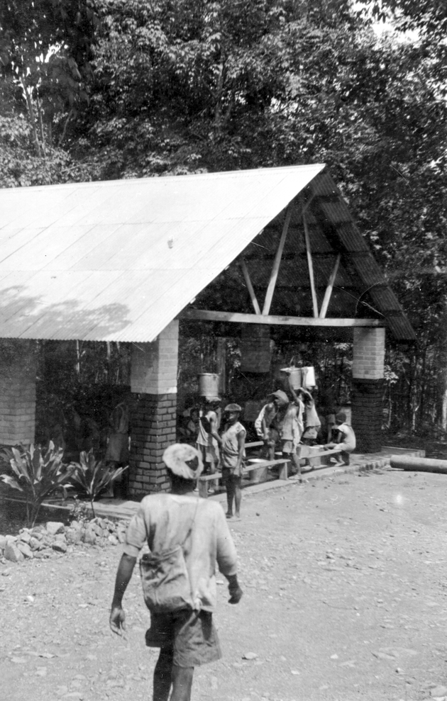 Photo: Plantation workers in open building (divisional collection station?).