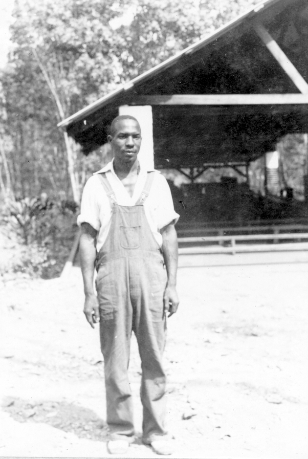 Photo: Liberian man in white shirt and overalls.