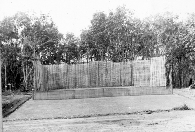 Photo: Reed or cane screens erected on three sides of a leveled earthen floor.