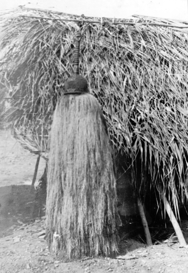 Photo: Masquerade sitting in front of a small thatched structure (kitchen or shrine?).