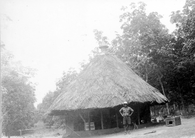 Photo: Liberian man in Western clothes posing in front of a round thatched house.