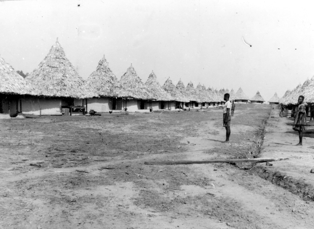 Photo: Twenty five or more round thatched houses closely set together on flat, cleared land with three Liberians standing. Good example of company built housing, almost military in its straight lines.