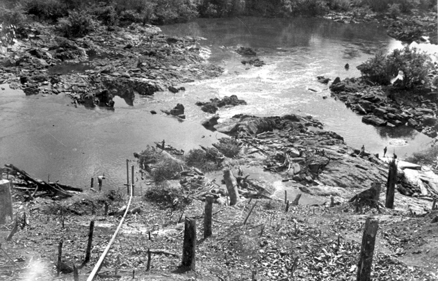 Photo: River rapids from above, tree stumps in foreground, three figures by the bank.
