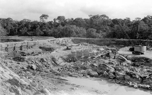 Photo: Construction project behind earthen dam (possibly a dam or bridge?) with a crane and truck.