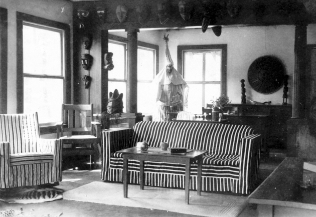 Photo: Manis residence interior with 15+ masks (shows Deangle costume for masquerade now in Harn collections).