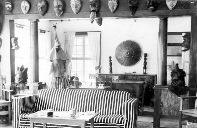 Photo: Manis residence interior with 12+ masks, Deangle costume for masquerade (now in Harn collections).