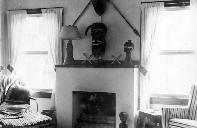 Photo: Manis residence interior with mask over fireplace, carved figures and other objects on mantle.