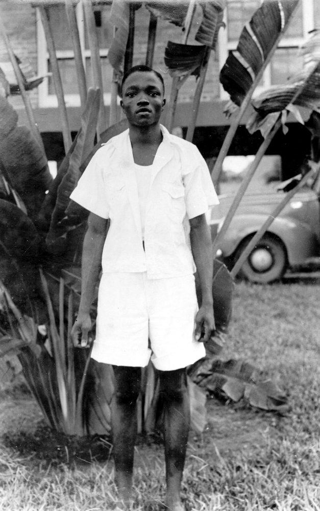 Photo: Young Liberian man posing in front of a Traveller's palm in residential garden.