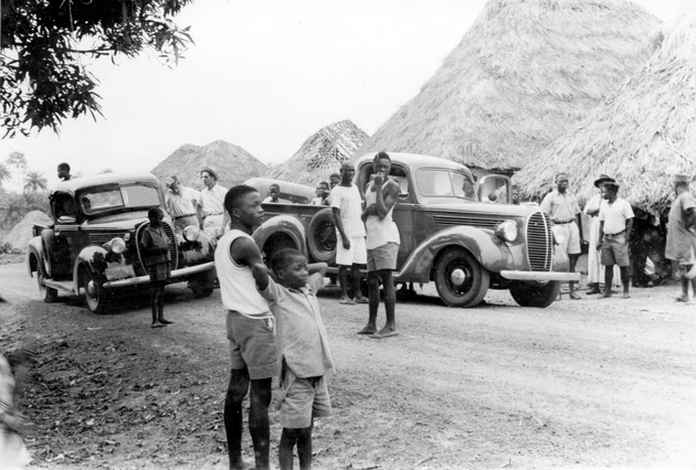 Photo: Roadside group of Liberian and American men with two pickup trucks near thatched roof houses.