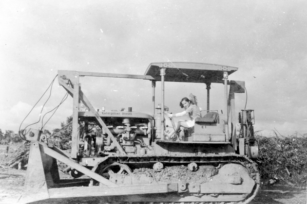 Photo: American woman posing on a Caterpillar Diesel bulldozer.