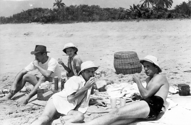 Photo: Three American men and an American woman at a picnic on the beach, three wear pith helmets. Manis is in left foreground.