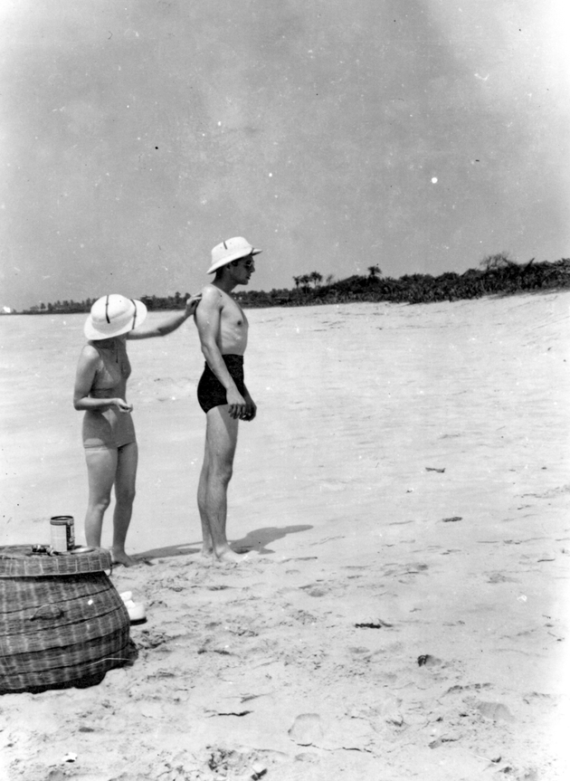 Photo: An American man and woman in pith helmets and bathing suits at the beach.