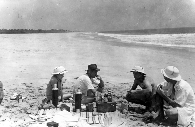 Photo: Four Americans, three men and a woman picnic on the beach, all wearing pith helmets or a hat.