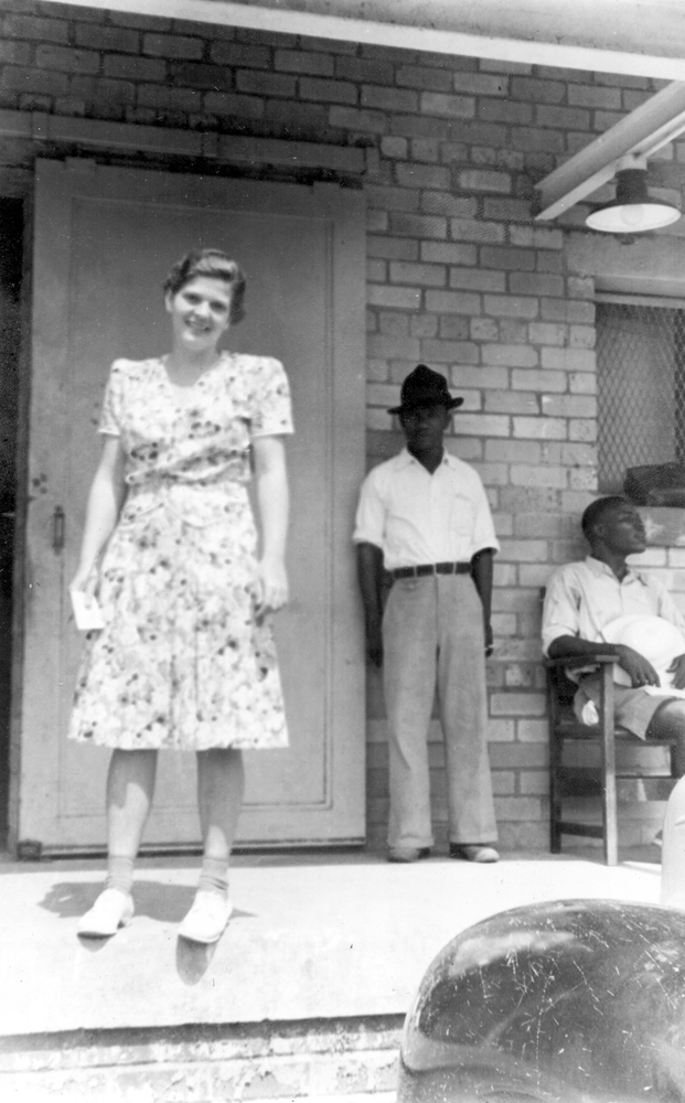 Photo. American woman on porch of a plantation building, two Liberian employees in background.