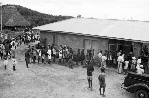 Photo: Long line of Liberian men entering a plantation building.