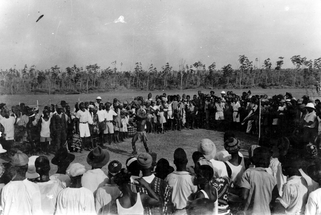Photo: A large group of Liberians and Americans watches a Snake Society acrobat toss child above his head.