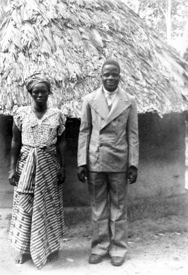 Photo: Liberian couple stands for (wedding?) portrait in front of round thatched roof house, man in Western suit.