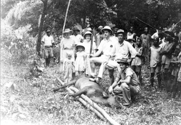 Photo: Three American men, two women, two children in fore with Liberians behind (one in uniform).