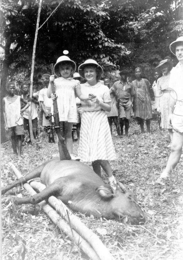 Photo: American girl about 6 years old in pith helmet stands on carcass holding rifle (with her mother?).