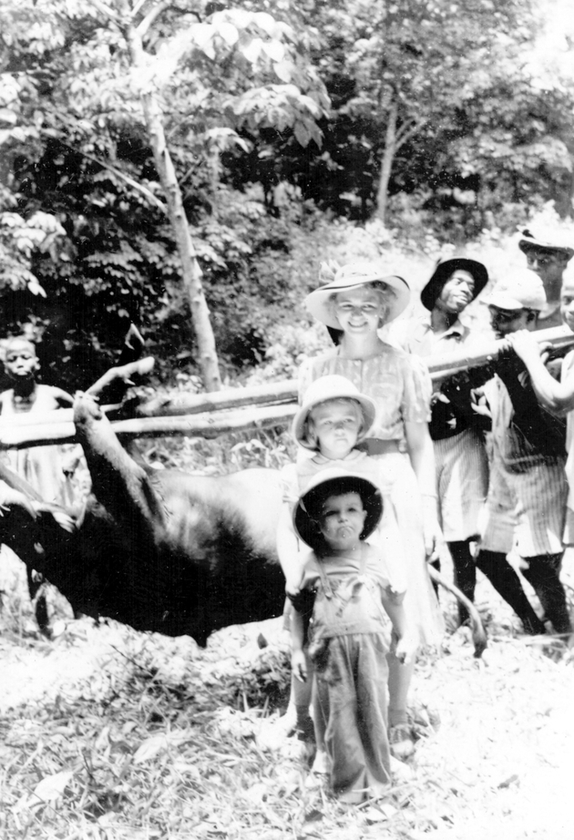 Photo: American woman and two children pose in front of raised buffalo trophy supported by Liberian men.
