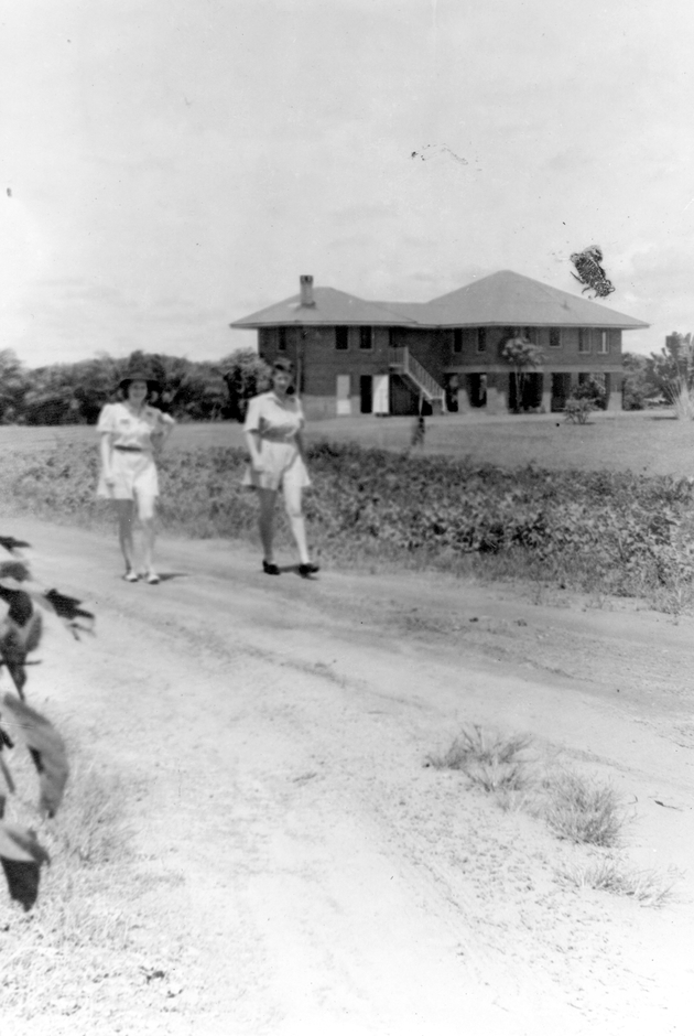 Photo: Two American women walking along a dirt road, Plantation residence in background.
