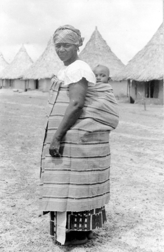 Photo: Liberian woman carrying a baby on her back, row of houses in background.