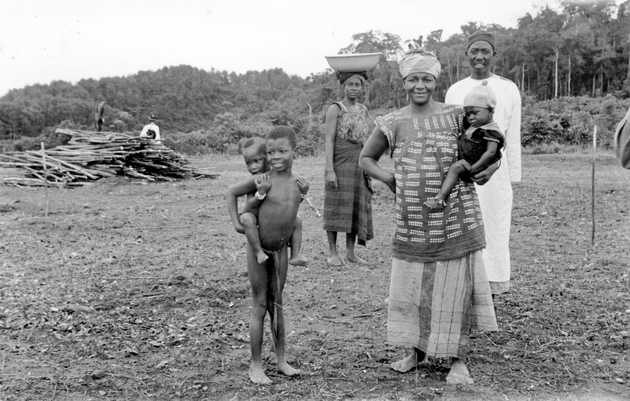 Photo: Two women, an adult man and three children in a cleared forest area.