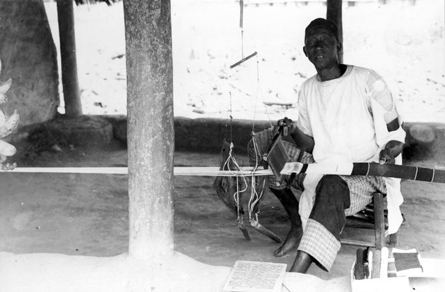 "Photo: Liberian man making ""men's weave"" strip cloth with a traditional loom."