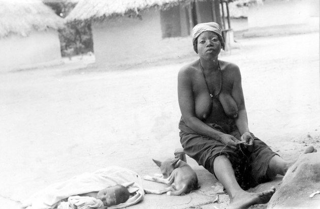 Photo: Seated woman beside a sleeping infant and dog. She wears chalk on her face, which is used as a traditional cure and after Sande initiations.
